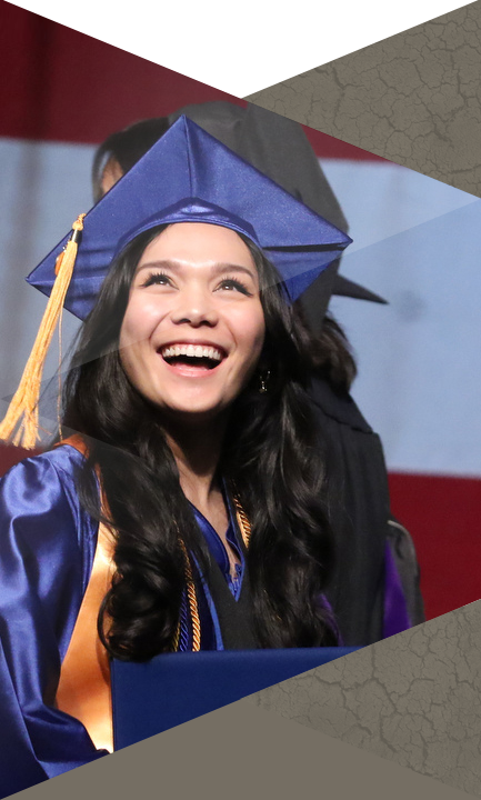 CSN Student standing on stage smiling after receiving diploma