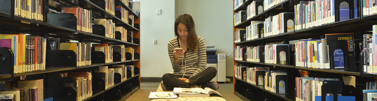 Girl in Library Aisle sitting on floor holding cell phone and reading books