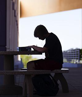 Student doing homework on outdoor patio table